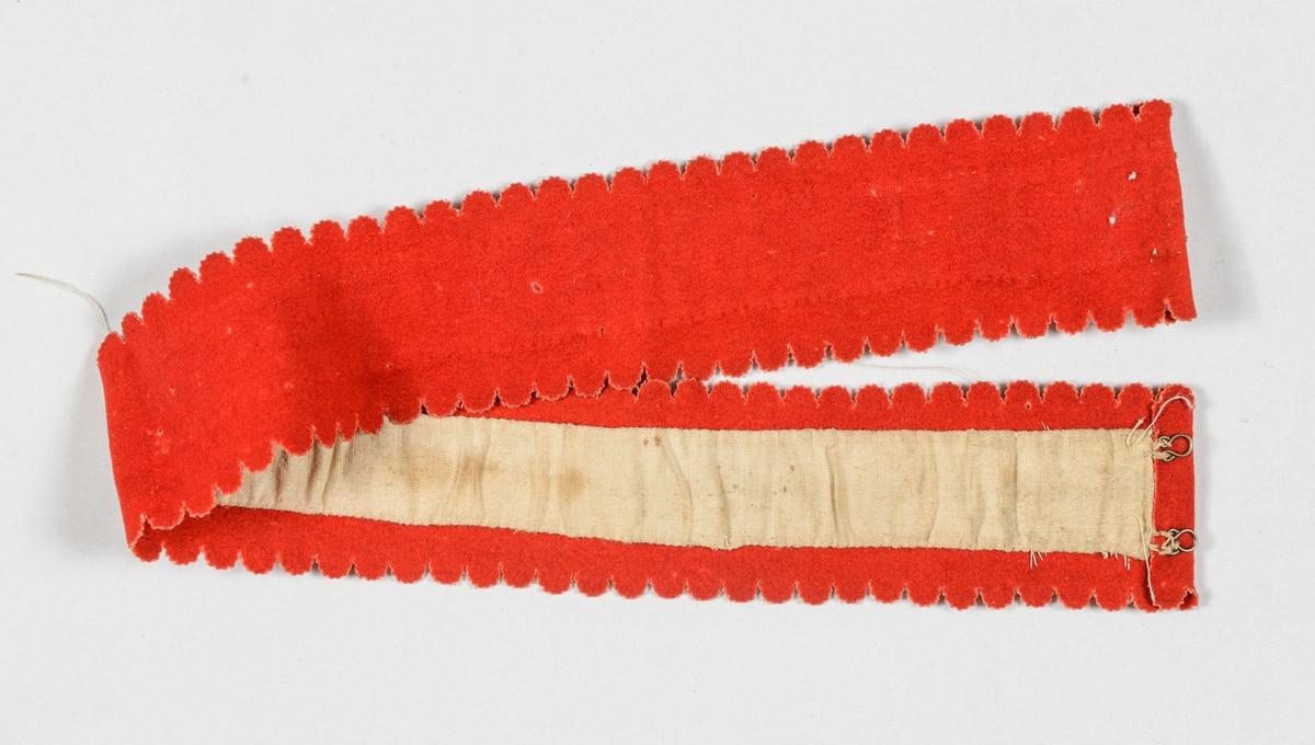 Belte med botn i rødt klede. Begynnelse på perlebroderi i eine enden. Langsidene har utstansa, taggekant med halvsirkler  ca 1 cm i diameter, endane er falda, og det er messinghekter og krokar i kvar ende på baksida. Manglar spenne. Fòra på baksida med ubleikt bomull.