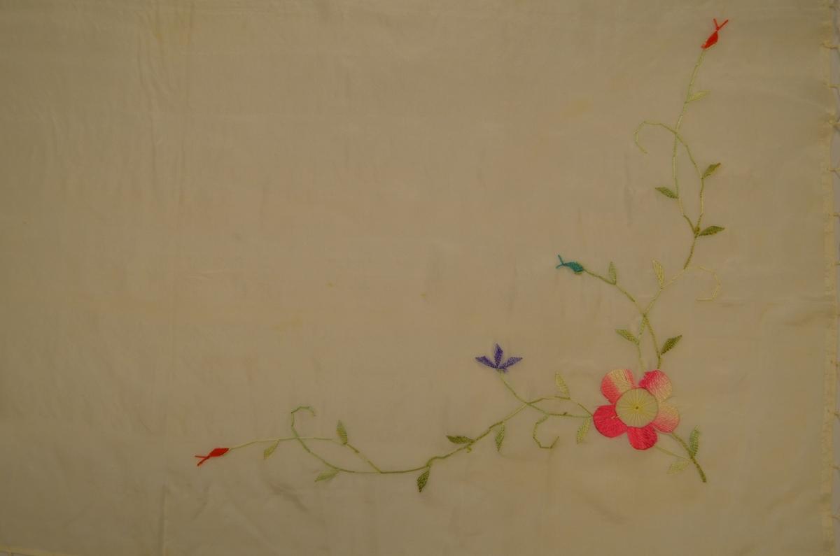 Tørkle i ubleikt silke med silkefrynser. I to hjørne broderte roser og greinar (plattsaum)  i rosa og grønfarger.