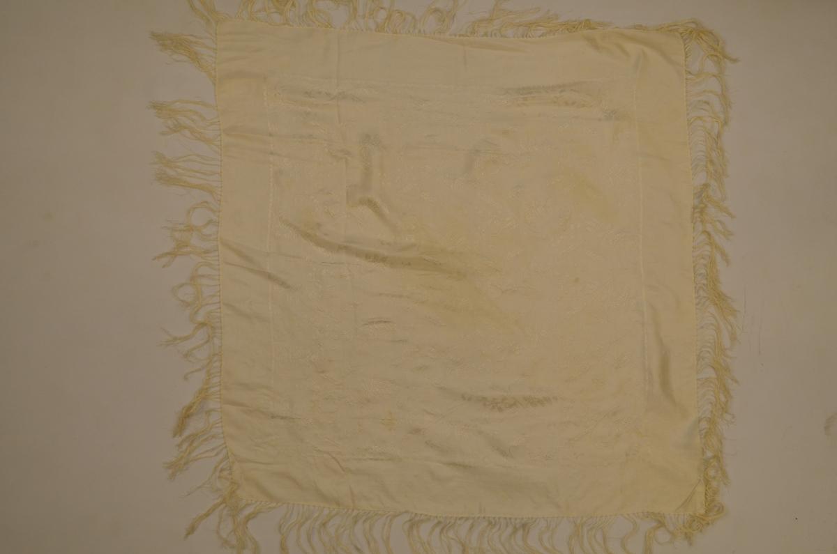 Tørkle i kvit silkedamask med rosemønster. Påsette frynser i beige 10,5 cm lange.