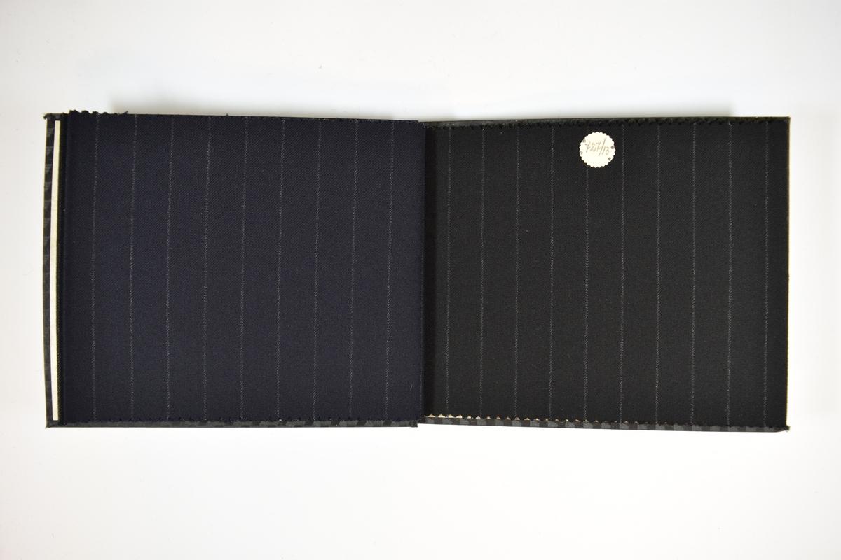 Prøvebok med 4 stoffprøver. Relativt tynne stoff med lyse vertikale striper. Kyperbinding/diagonalvevd. Stoffene ligger brettet dobbelt slik at vranga skjules. Stoffene er merket med en firkantet papirlapp, festet til stoffet med metallstifter, hvor nummer er påført for hånd.   Stoff nr.: 727/11, 727/12, 727/13, 727/14.