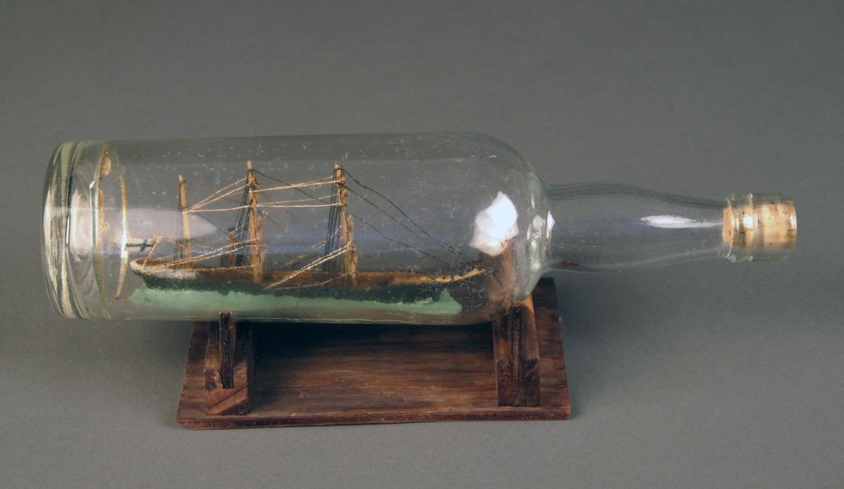 3- mastet seilskip i flaske. Malt bakgrunn av landskap med hvite murhus og himmel.  Flasken er av lysegrønt glass, formen er avrundet firkantet, og har en grønn skrukork. Flettet hvitt tau rundt flaskehalsen. Flaska står på et stativ av brunbeiset tre.