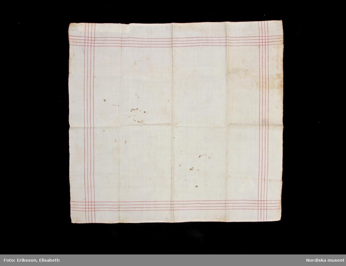Näsduk av vit bomullslärft med kantbård av 4 invävda röda trådar, maskinsydda fållar på 2 sidor, 2 stadkanter. Märkt i ena hörnet R J  med vitt lingarn. /Berit Eldvik 2010-09-17