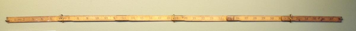 Sammenleggbar tommestokk på ein meter, med centimentermål på den eine sida, og norsk tommemål på den andre.