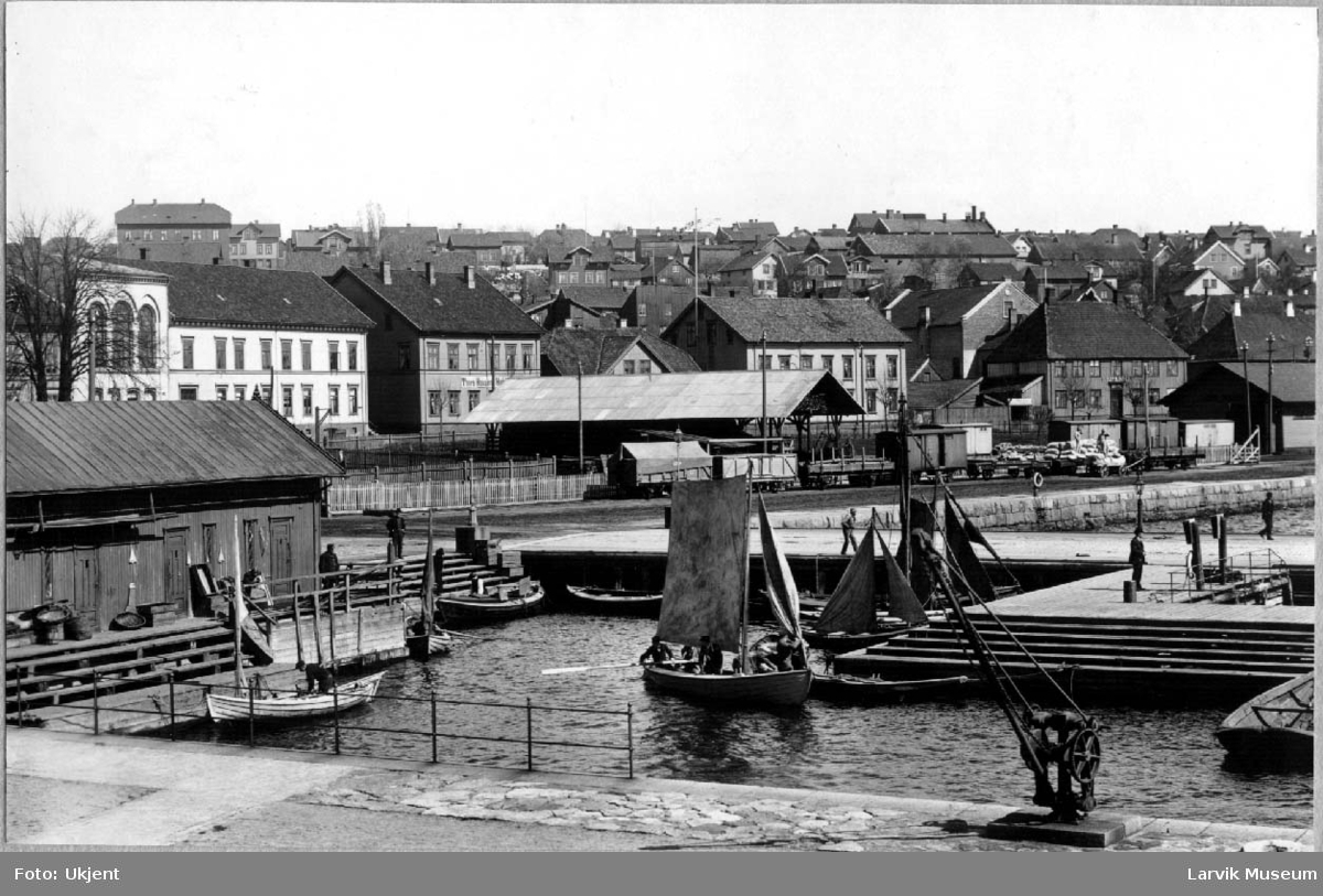 Byprospekt, bebyggelse, Larvik, sjøsiden, jernbanen, Storgata med Festiviteten og Thora Hansens hotell, småbåter på havnen, noen med seil.