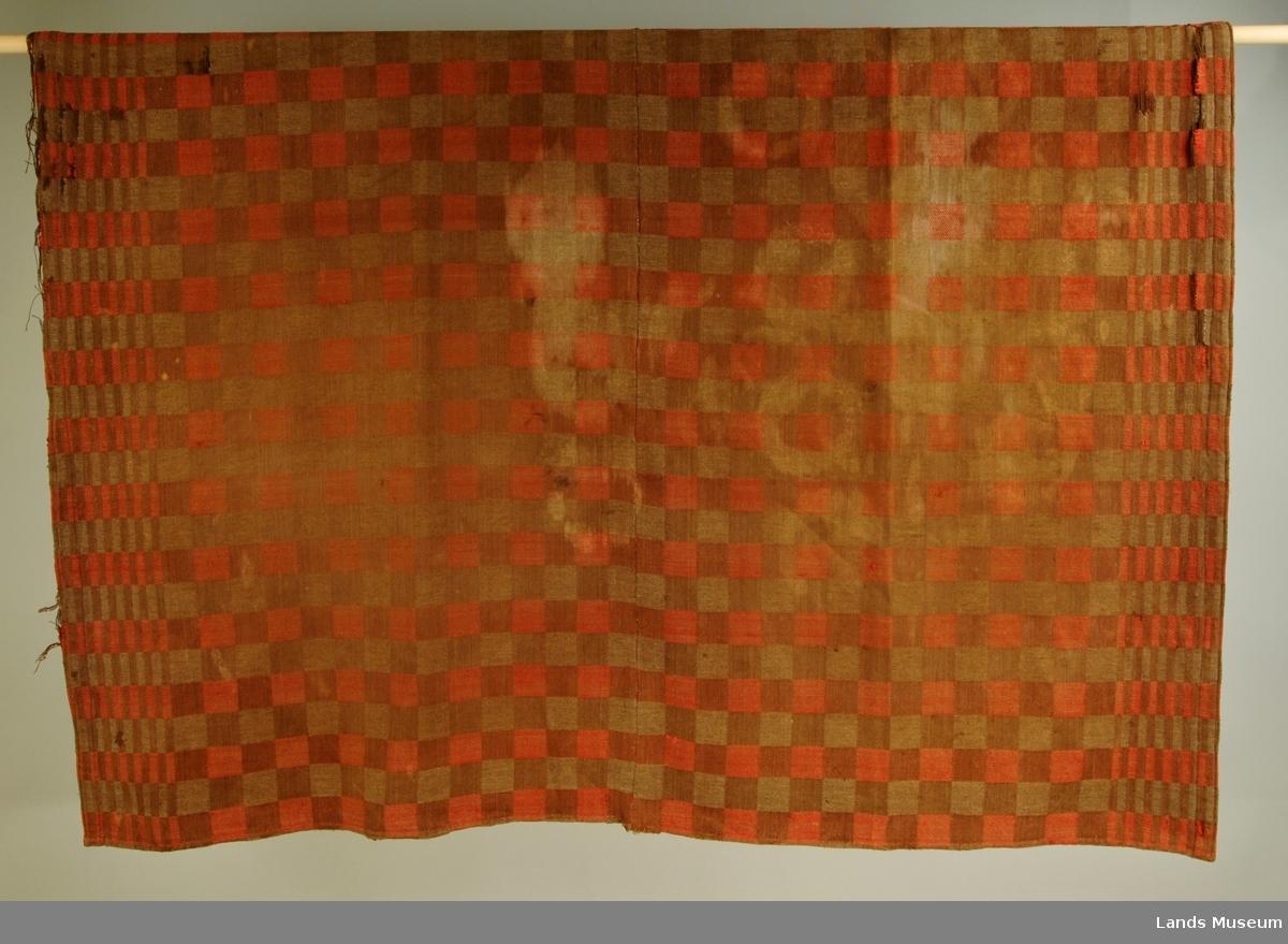 Dreiesvevd i dambrettruter. Rutene i mønsteret er ca 4 x 4 cm. Sydd saman på midten av to deler. Kanta med rødt bånd. Hjemmevevd.