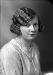 Ateljébild på en kvinna i klänning med spetskrage. Beställar