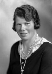 Ateljébild på en kvinna i pärlhalsband och spetskrage. Bestä