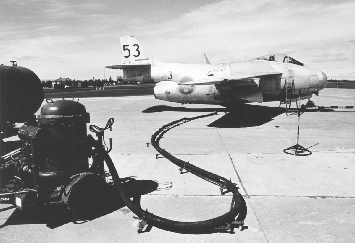 Flygplan J 29 Tunnan tillhörande F 3 Malmen tankas på F 4 Frösön flygfält. Kanslihuset med sitt valmade tak och värmecentralens skorsten syns i bakgrunden.