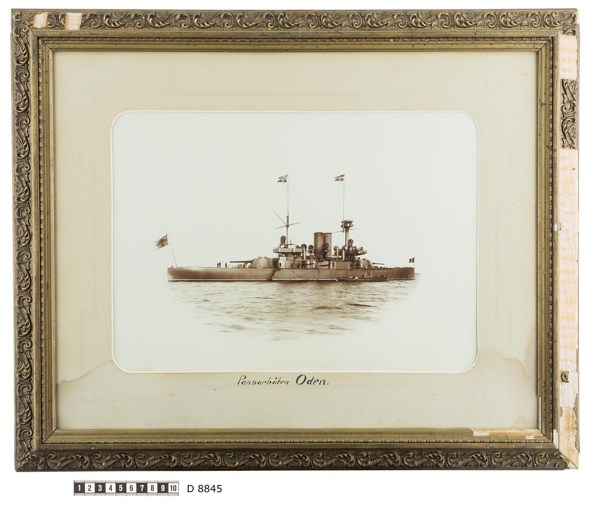 Fartygsporträtt som visar pansarbåten Oden till ankars. Fartyget syns från babordssidan där ett mindre ångbåt ligger förtöjt. Flera repstege leder upp till däcket. På akterdäcket står tre men som verka samtala.