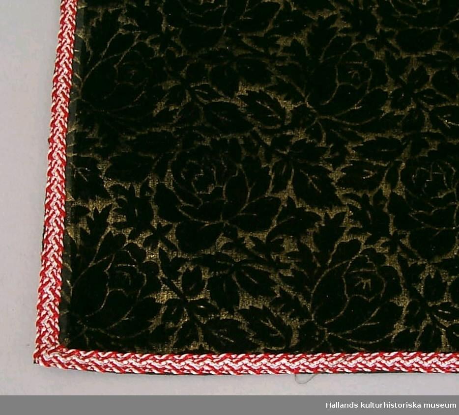 Rektangulär duk av mönstrat sammetstyg. Mönstret är bestående av svarta rosartade blommor på guldfärgad botten. Baksidan svart, med visst genombrott av samma mönster. Duken kantad av rödvitt, smalt band.