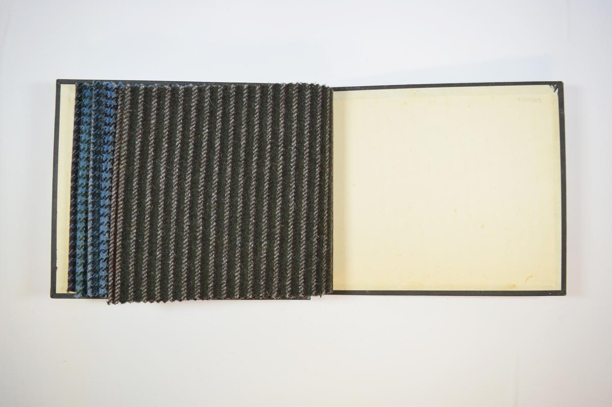Rektangulær prøvebok med seks stoffprøver og harde permer. Permene er laget av hard kartong og er trukket med sort tynn tekstil. Boken inneholder middels tykke flerfargede stoff med rute- eller stripemønster. Kyperbinding/diagonalvevd. Stoffene ligger brettet dobbelt i boken slik at vranga skjules. Stoffene er merket med en firkantet papirlapp, festet til stoffet med metallstifter, hvor nummer er påført for hånd.   Stoff nr.: 2065/1, 2065/2, 2065/3, 2065/4, 2065/6, 2065/7.