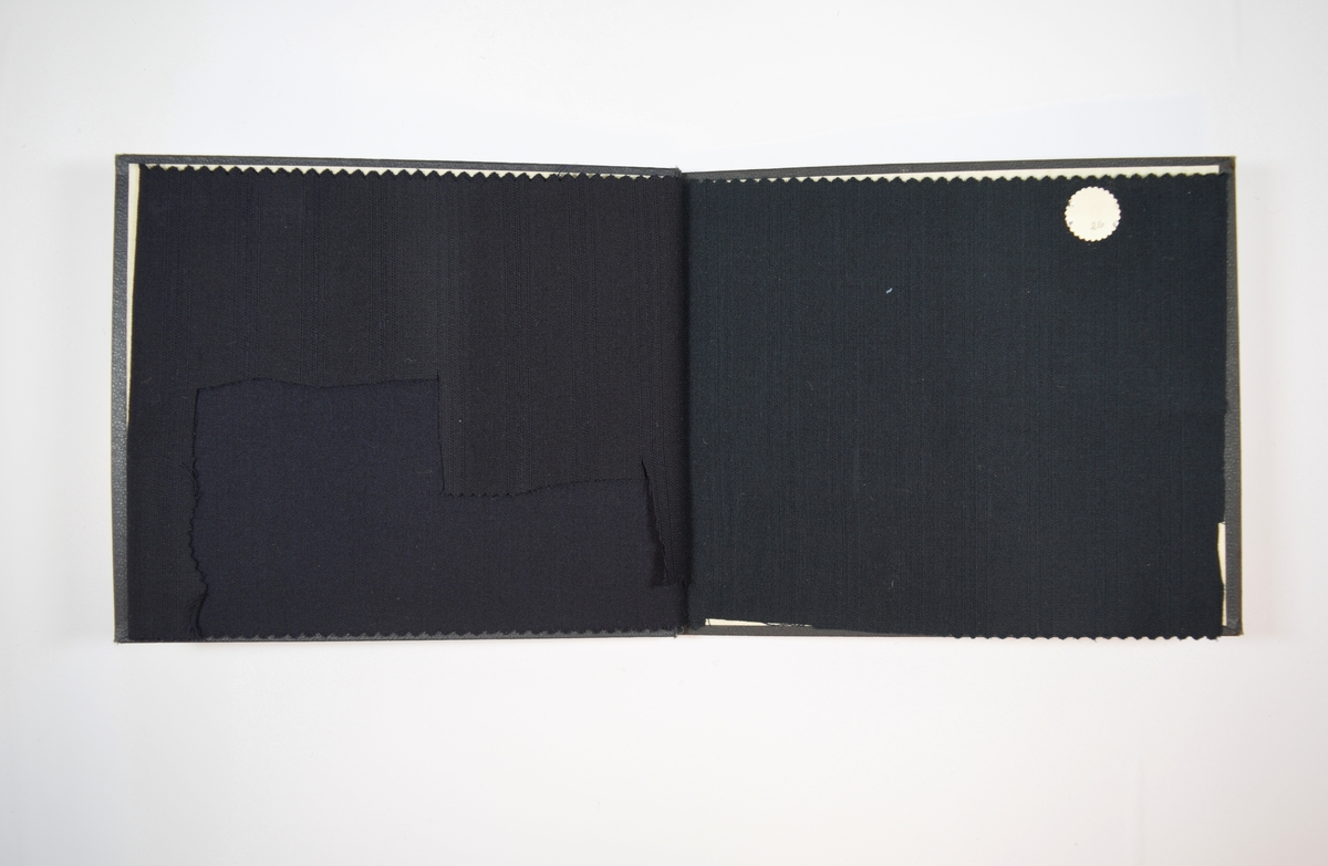 Rektangulær prøvebok med to stoffprøver og harde permer. Permene er laget av hard kartong og er trukket med sort tynn tekstil. Boken inneholder relativt tynne men tette stoff med samme stripemønster i veven, men med ulike farger. Ensfargede stoff. Baksiden/vranga er mye jevnere uten særlig stripemønster. Stoffet ligger brettet dobbelt i boken slik at vranga skjules. Stoffet er merket med en rund papirlapp, festet til stoffet med metallstifter, hvor nummer er påført for hånd. Innskriften på innsiden av forsideomslaget indikerer at begge stoffene i boken har kvalitetsnummer 2110.   Stoff nr.: 2110/25, 2110/26.