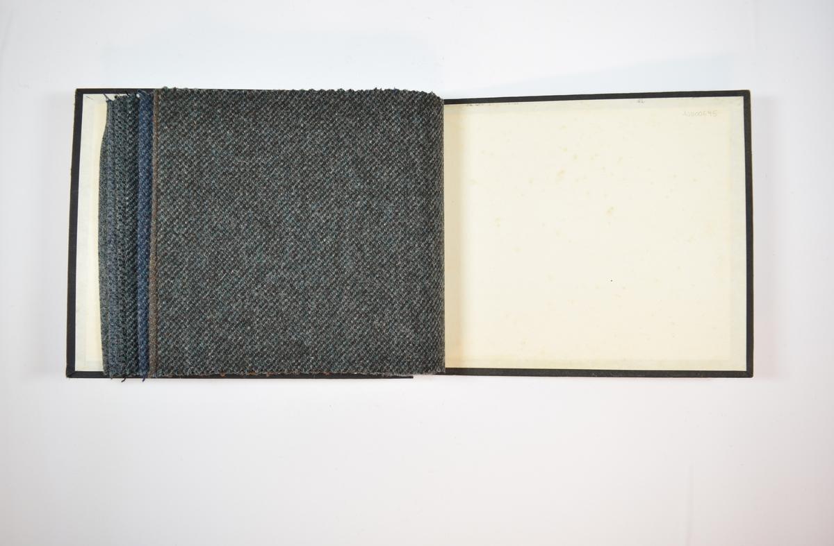 Rektangulær prøvebok med syv stoffprøver og harde permer. Permene er laget av hard kartong og er trukket med sort tynn tekstil. Boken inneholder middels tykke flerfargede stoff med utydelige skrå striper. Kyperbinding/diagonalvev. Alle stoffene ligger brettet dobbelt i boken slik at vranga dekkes. Stoffene er merket med en firkantet papirlapp, festet til stoffet med metallstifter, hvor nummer er påført for hånd.   Stoff nr.: 3000/22, 3000/23, 3000/24, 3000/25, 3000/26, 3000/27, 3000/28.