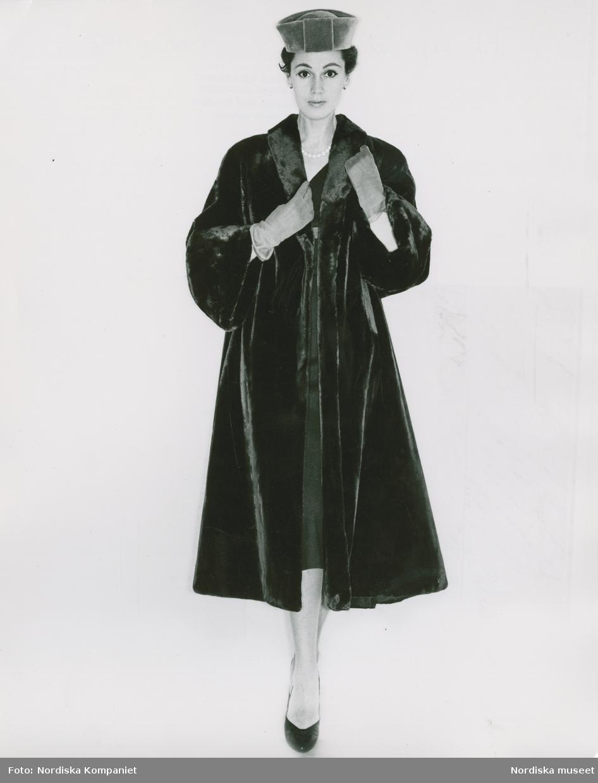 Modell i pälskappa, pälshatt, handskar, halsband och pumps.