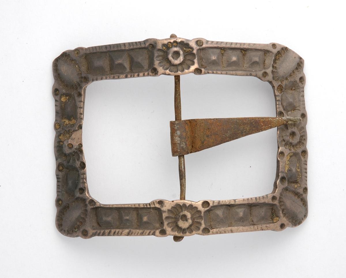 Skospenne i støypt bronse. Rektangulær form med avrunda  hjørne. Konveks. På midten tverrgåande stong med påfesta tann  i smidd jern. Kalven manglar. Pedant til VFF 00539.