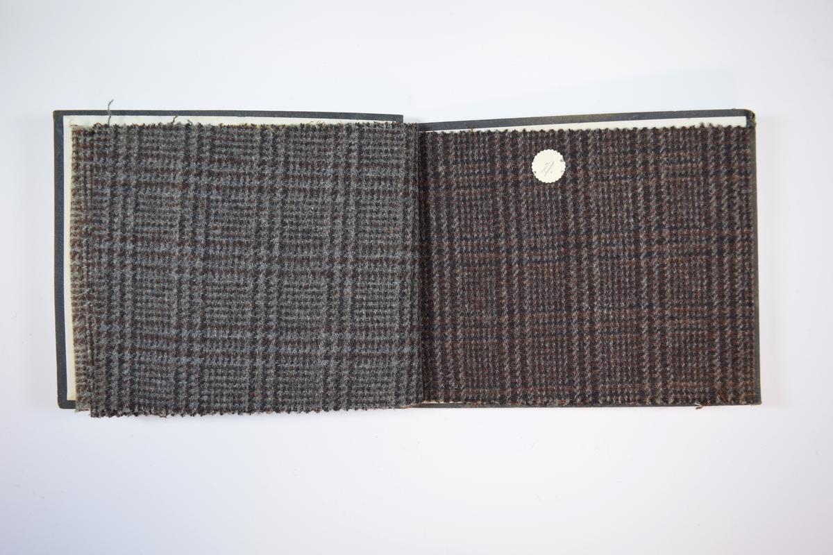 Rektangulær prøvebok med harde permer og fire stoffprøver. Permene er laget av hard kartong og er trukket med sort tynn tekstil. Boken inneholder middels tykke ullstoff med rutemønster. Kyperbinding/diagonalvev. Stoffene ligger brettet dobbelt i boken slik at vranga skjules, men mønsteret er det samme på baksiden. Stoffene er merket med en rund papirlapp, festet til stoffet med metallstifter, hvor nummer er påført for hånd. Innskriften på den første lappen indikerer at alle stoffene i boken har kvalitetsnummer 5067.   Stoff nr.: 5067/18, 5067/19, 5067/20, 5067/21.
