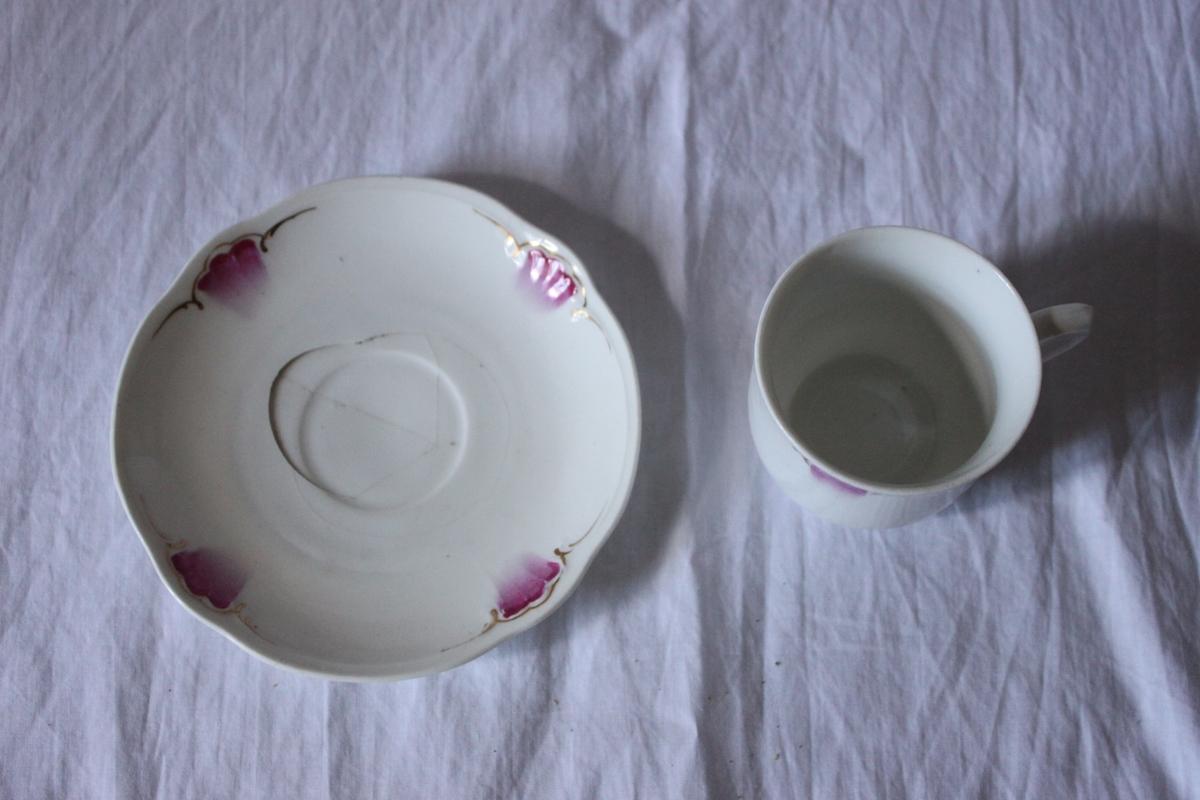 Kaffefat av porslin, svagt kupad. Målad dekor i form av kallrosa, tulpanliknande blomma med guldslinga.