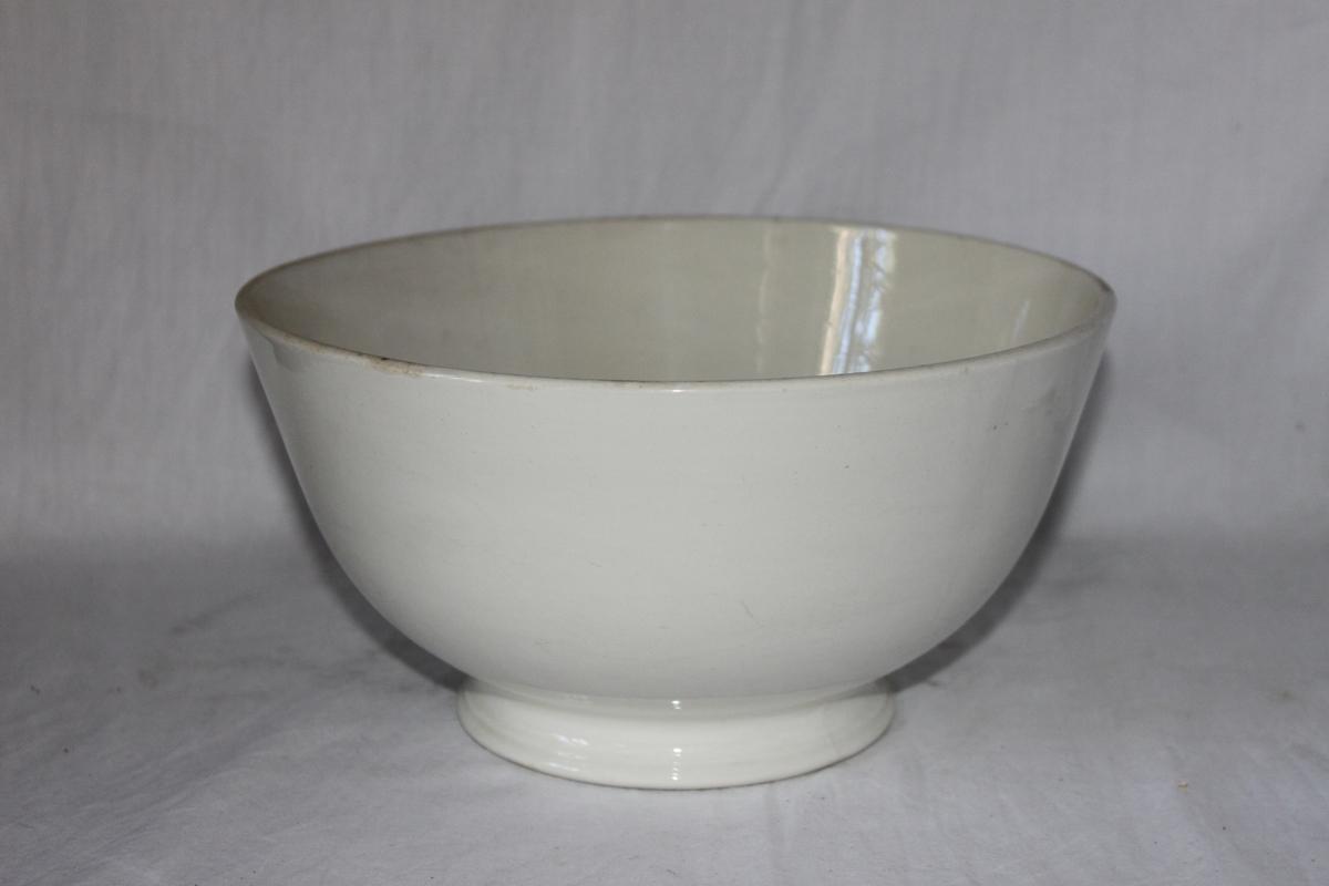 Skål av vitt glaserat flintgods. Mjukt skålformad, stående på 20 mm hög och 130 mm vid fot.