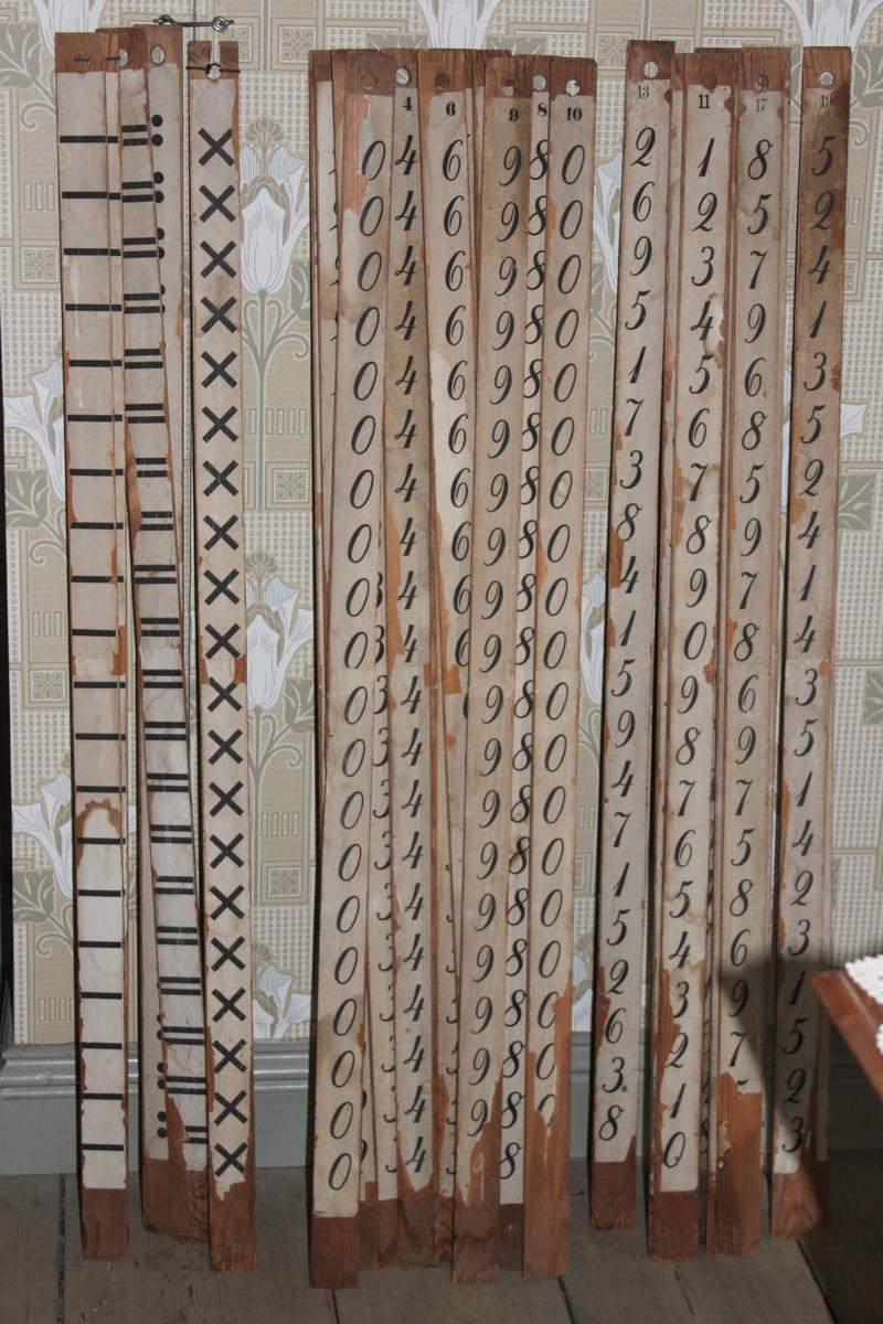 Räknestav i trä med påklistrad pappersremsa. Denna stav har siffror längs hela staven.