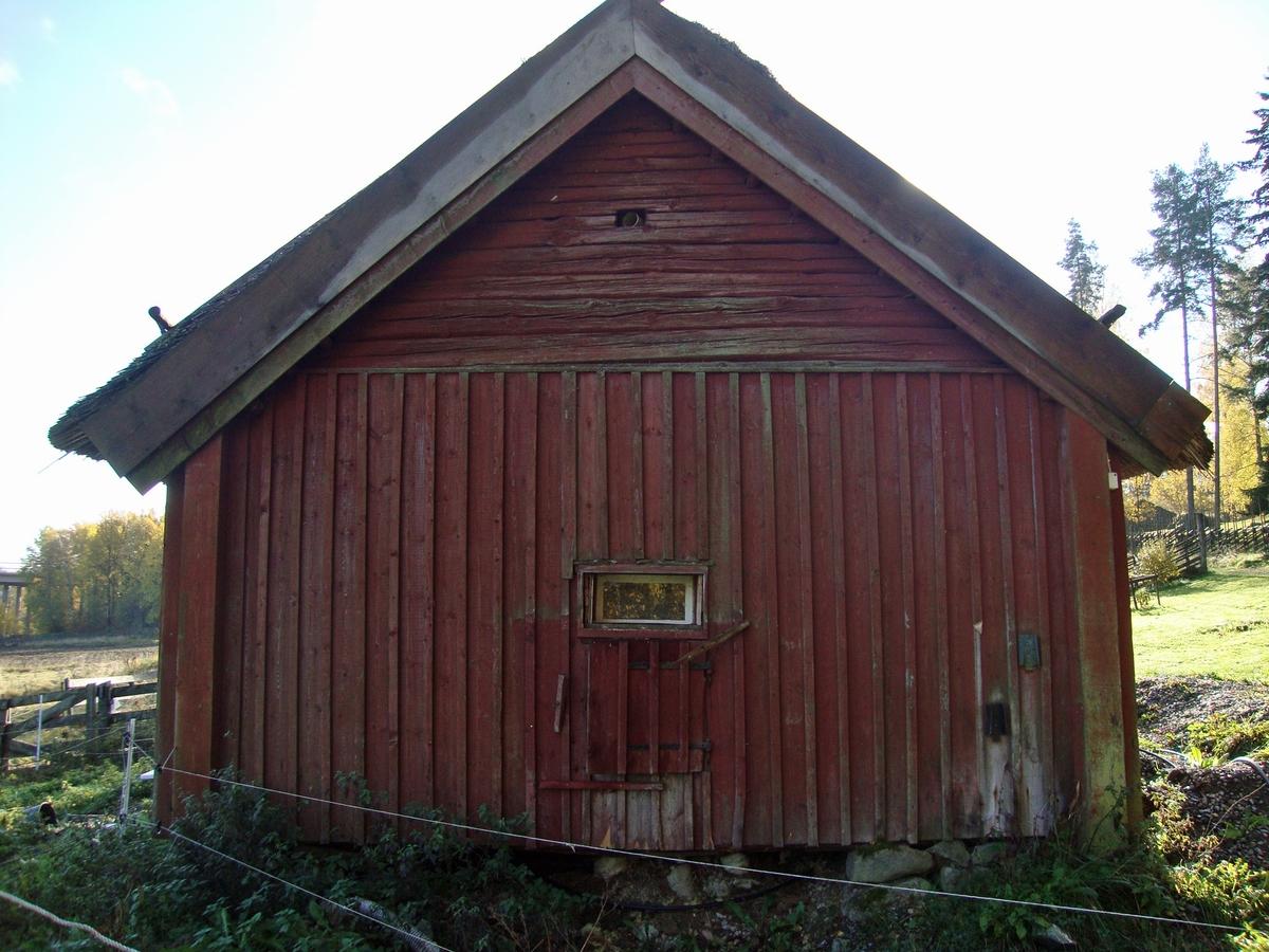 Ladugården är byggd av liggande timmer på en grund av hörnstenar och med utfyllnad av spräckt fältsten. Knutarna skyddas av knutlådor. Den undre delen av gavlarna är klädda med locklistpanel. Den ursprungliga rumsindelningen är förändrad, då byggnaden fram till tidigt 2000-tal använts för djurhållning. I den norra delen av ladugården har tidigare funnits en fähusdel med lane innehållande två bås för kreatur samt förvaringsutrymme för foder ovanför dessa. Troligen har det även funnits en kätte för mindre djur. Utrymmena i den mellersta och södra delen av byggnaden har tidigare upptagits av en logkista för tröskning samt ett loggolv, även kallad lada, för förvaring av säd. Huskroppen har en genomgående skarv placerad i det som tidigare varit lanen och byggnaden har alltså någon gång under årens lopp varit delad eller blivit påbyggd. Skarven är hophållen av bultade plattjärn. Den fanns före flytten till Vallby Friluftsmuseum och syns på ett foto från ursrungsplatsen, taget före 1923. Byggnaden genomgår under 2012-2014 en restaurering för att iordningställa en torpmiljö som ska skildra en soldats liv vid sekelskiftet 18-1900. Rumsindelningen kommer att återställas. Den västra långsidan har idag en ingångsdörr till det som tidigare varit lanen. Fähusdelen har små rektangulära och kvadratiska fönster åt väster, norr och öster. Den norra gaveln har även en gödsellucka placerad alldeles under fönstret Logkistan har två öppningar, en på vardera långsidan. Den västra är tillsluten med en öppningsbar lucka, den östra har en stor öppning med löstagbara stockar underst samt två öppningsbara luckor. Tröskningen skedde med slagor. Luckorna i logkistan öppnades vid rensningen av den tröskade säden, varvid drag uppkom i utrymmet och agnarna blåste åt sidan. Takkonstruktionen består av tre gavelrösten, varav en inuti byggnaden. Detta p g a byggnadens utökning. Takstolen är stående på stocken under remstycket. Taktäckningen är ett ståltrådsbundet stråtak med vass och ryggning av halm 