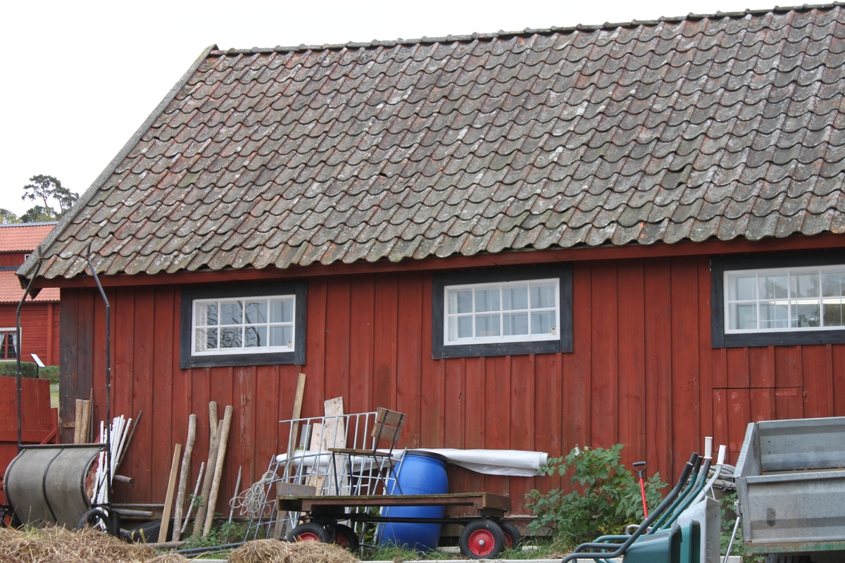 Byggnaden är uppförd i stolpverkskonstruktion, på huggna hörnstenar. Grunden täcks av plankor. Yttervägg av locklistpanel. Sadeltak med branta takfall. Undertak av brädor, lagda horisontellt. Takbeklädnad av enkupigt tegel. Vindskivor och vattbrädor i trä. Liggande fönster längs norra långsidan, spröjsade med åtta glasrutor. Lunettfönster på östra gaveln, vindsvåningen. Skärmtak på stolpar utefter södra långsidan, med beklädnad av brädor. Innergolv av cement i hela byggnaden. Innervägg mellan rummen av brädor. Ytterväggarna i rummet klädda med skivor. Taken är av brädor. Hela byggnaden inredd för djurhållning, med boxar, spolplatta, förvaringsutrymmen m m.