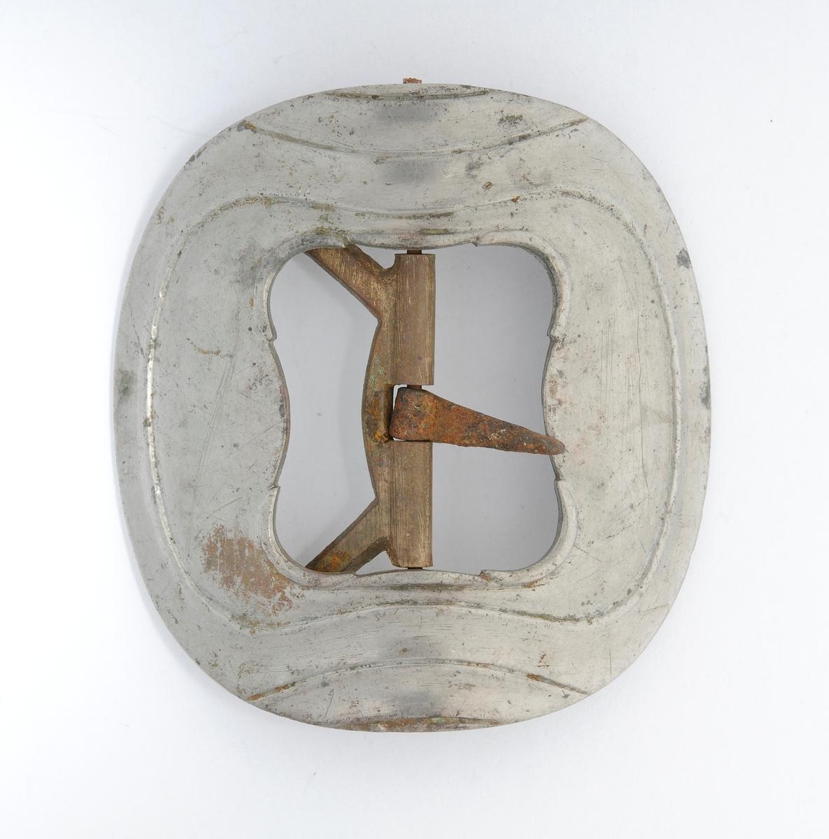 Spenne i støypt messing, firkanta med runde hjørner. Stolpe, tann og kalv i smidd jern.