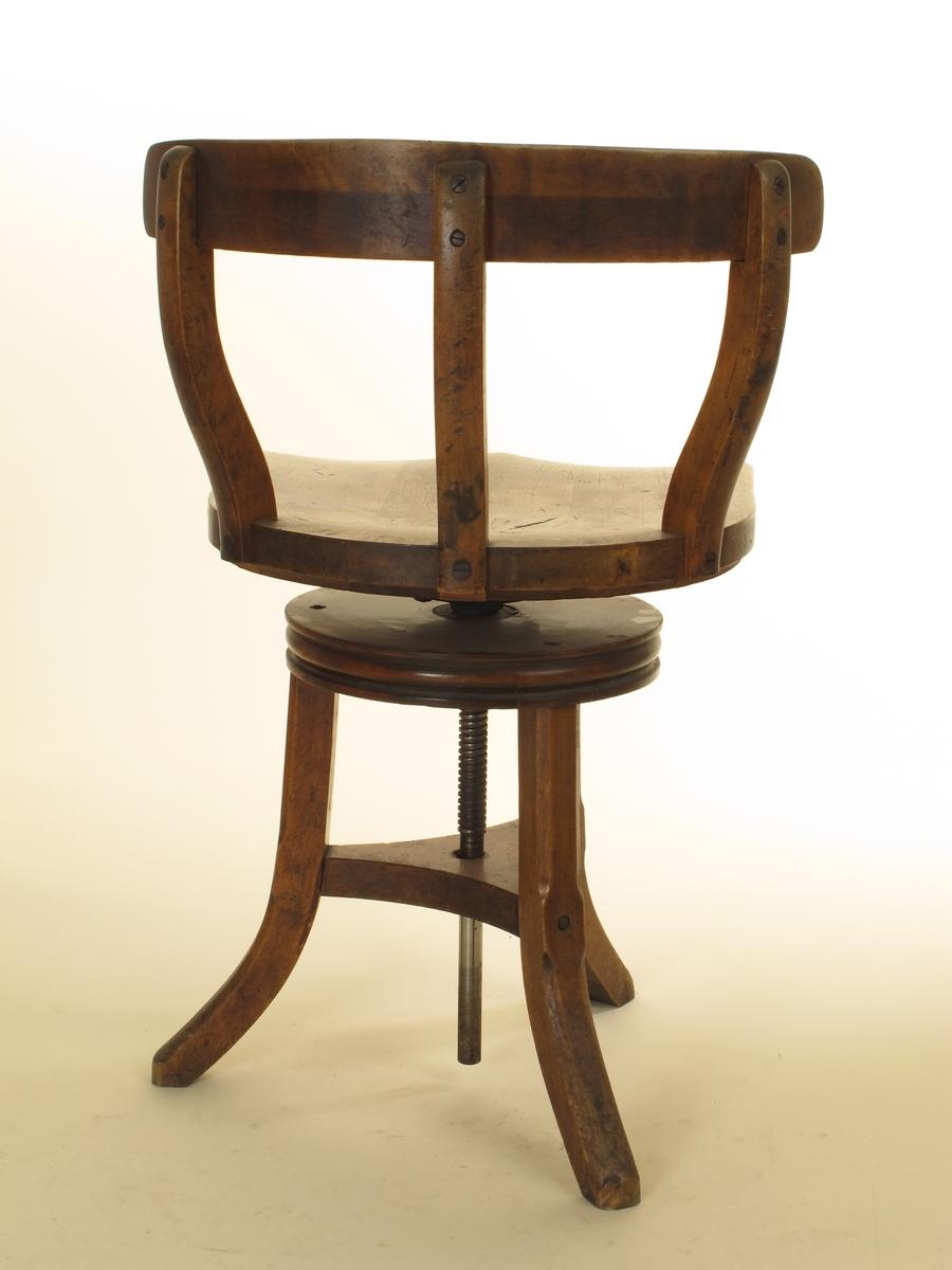 Dreibart sete med lav, svungen, horisontal rygg, på trefotet understell. Kan tas fra  hinannen i to deler. Beiset, svakt polert eller fernissert.