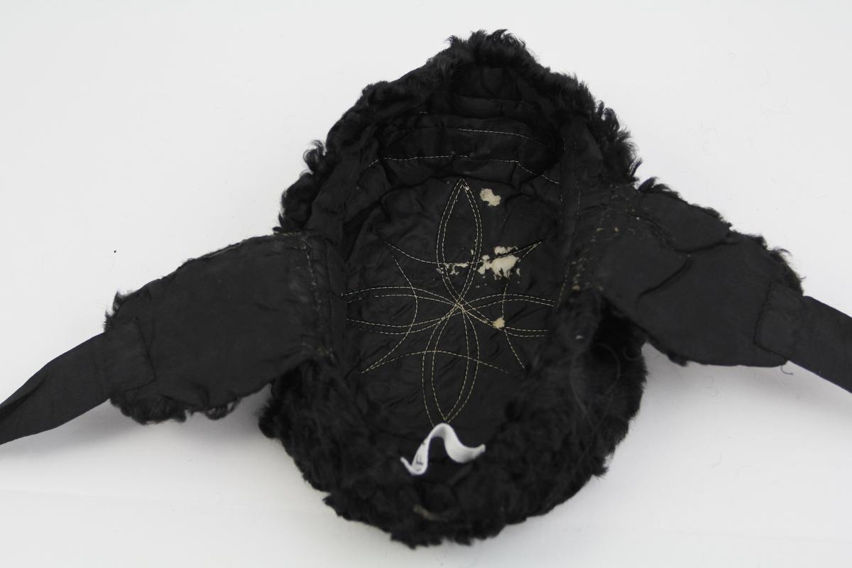 Form: Kileformet med sidestykker og øreklaffer med knyttebånd.  Rund og flat topp. Søm i foret på innsiden som former en blomst/stjerne.
