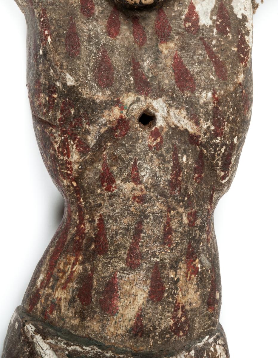 Kat. kort: Krucifix, s.k. processionskrucifix, från 1400-talets början? Figuren synes ha varit förgylld, bloddroppar målade över hela kroppen. Kring höfterna ländkläde; törnkrona som verkar rullad duk el. dyl. Tvådelat skägg, hår och skägg svarta. Ena foten skadad. Själva korset saknas.