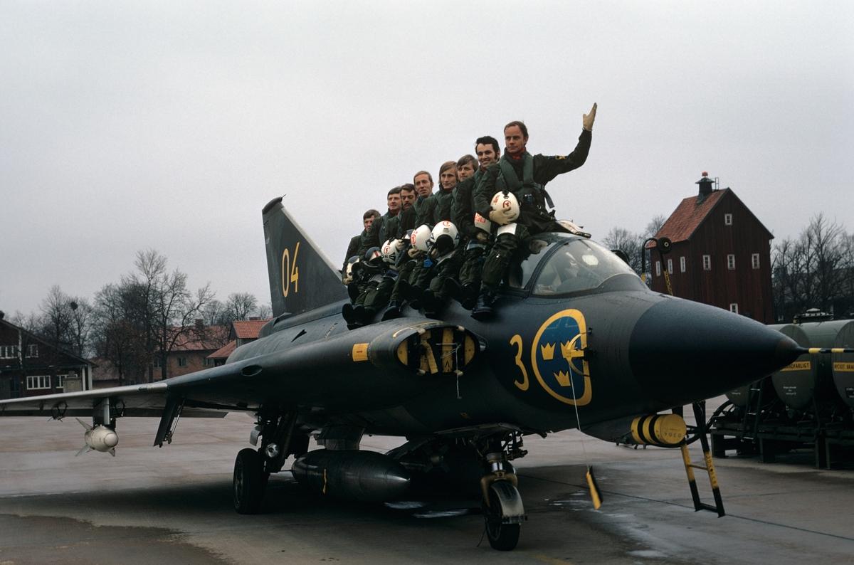 Flygförare ur en flygdivison på F 3 sitter på flygplan J 35F. 8 militärer på flygplanets rygg. Bildserie om två bilder.