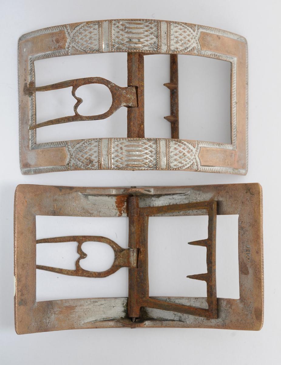 Skospenne, A og B i støypt messing.  Rektangulær og bua form. Dekorert overflate, men med flatt stykke på kortsidene og litt innover langsidene. Stolpe, tann og kalv i smidd jern. Tanna har to piggar.