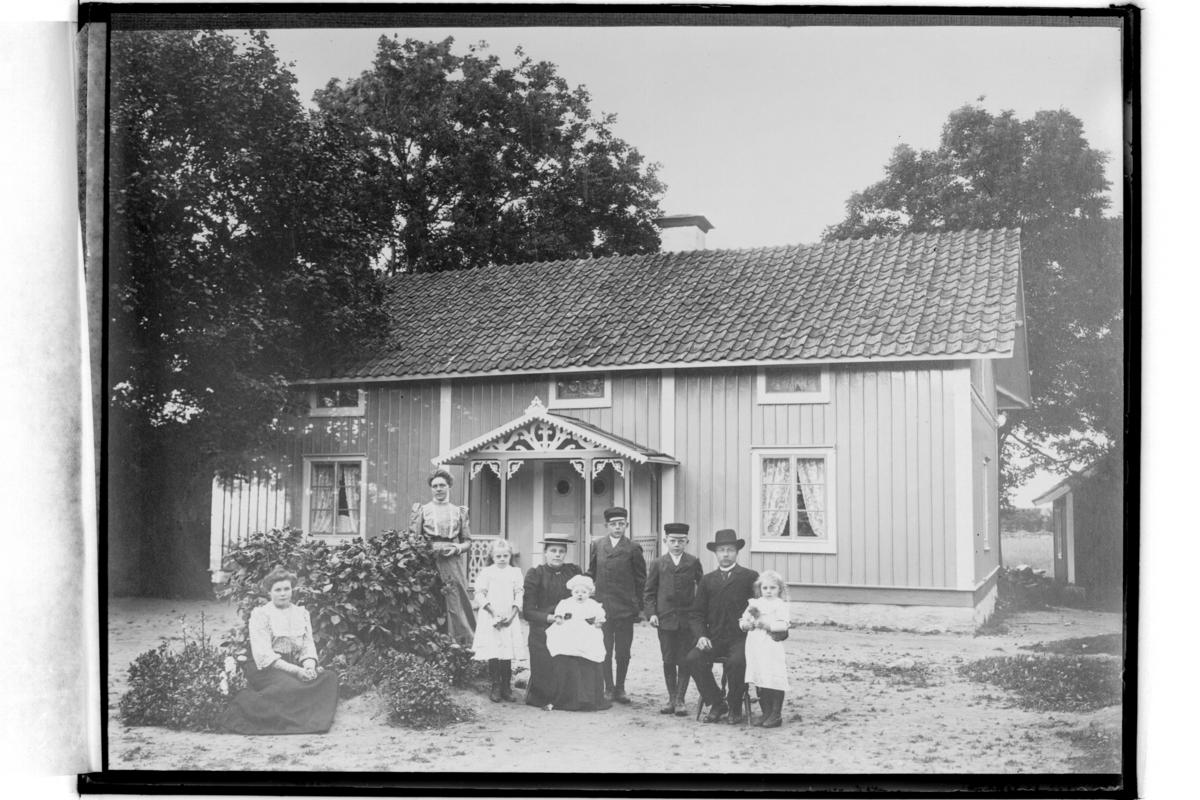 En och en halvplans bostadshus med veranda i snickarglädje. 9 personer framför huset.Aug. Andersson(Reproduktion 1934)
