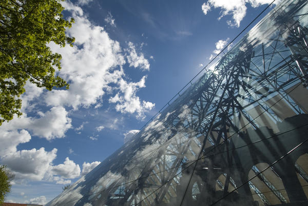 Hvite skyer speiler seg i glasset på vernebygget mens silhuetten av domkirkeruinen skimtes bak glasset.. Foto/Photo