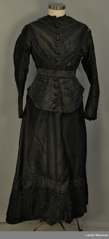 Brudekjole i svart silke. Overdelen har 10 svarte knapper i front, 2 hemper. Dekor langs baksiden av ermene. Skjørtethar hemper bak. Rynkete på nedre delen.