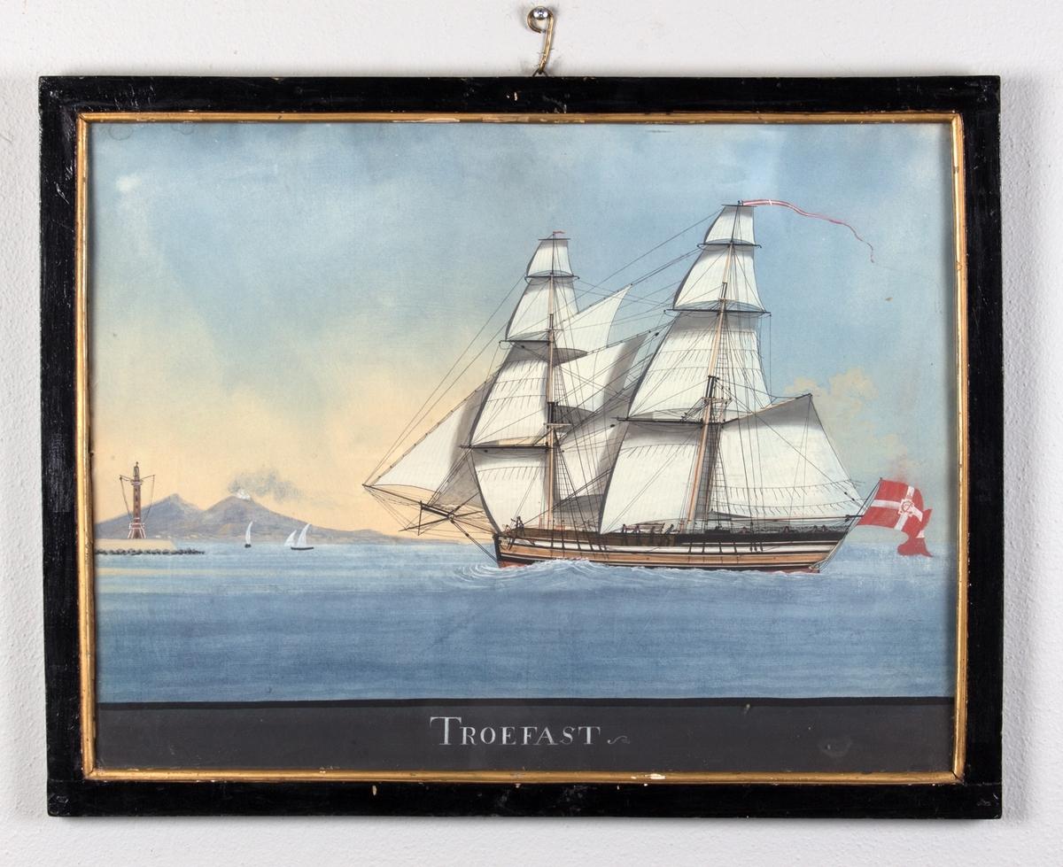 Briggen TROEFAST med full seilføring, ved innseiling til Napolibukta med Vesuvs i bakgrunnen. Skipet fører dansk flagg med kongelig monogram i akter, og vimpel i masten.