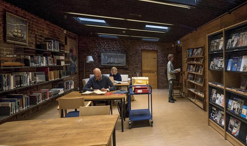 To personer sitter på lesesalen og en person står ved bokhylle på biblioteket.