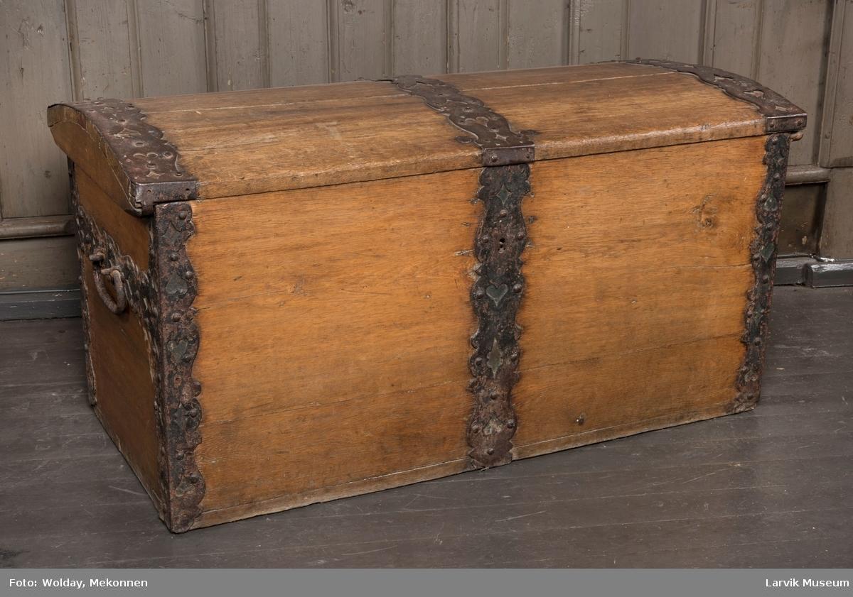 Kiste med buet lokk, rette sider. Leddik til høyre. gj.br. jernbeslag på lokket, i hjørnene og på sidene. Jernhengsler med beslag. Jernhåndtak i sidene