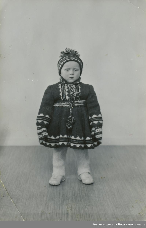 Bjørg Feldt som barn, oppstilt med hjemmestrikket drakt bestående av kofte, lue og votter.