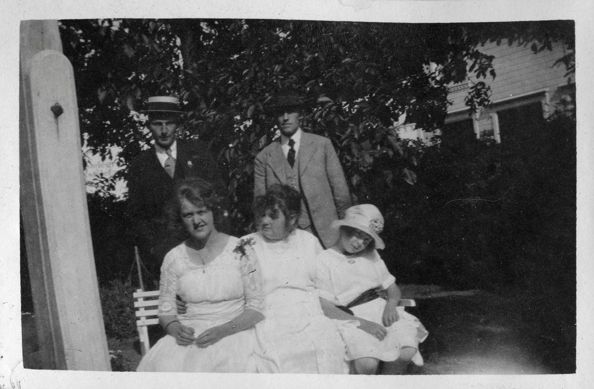 """Gruppe mennesker på en benk i hagen ved Grand Hotel, Lillesand 1921. Bildetekst: """"Lillesand, 1921"""""""