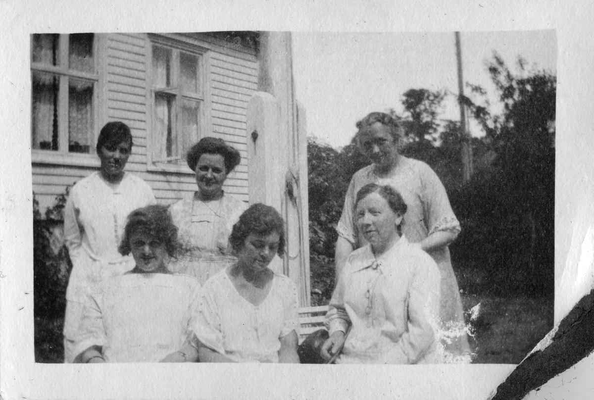 """Gruppe mennesker på en benk i hagen ved Grand Hotel, Lillesand 1921. Bildetekst: """"Lillesand, sommere"""