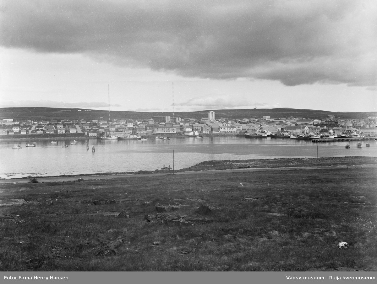 Motivet viser vestre del av Vadsø sentrum og havna sett fra Vadsøya 20.07.1968. Øverst i midten av bildet ser en de to radiomastene, Fylkesbygget, Statens hus, Prestegården og Vadsø kirke. Helt til høyre i bildet sees dampskipskaia. På havna og ved kaianleggene sees store og små fiskebåter.  I forgrunnen ser man en del av veien som går fra brua til Sildoljefabrikken på Vadsøya.