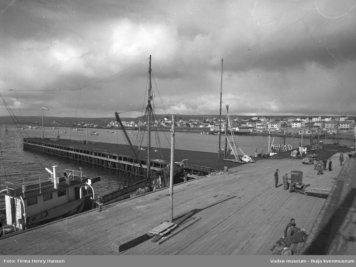 Vadsø 1952. Dampskipskaia. Bildet er tatt mot nordøst og viser Midtbyen og Ytrebyen, med overskyet himmel. Kaien er i forgrunnen, både landsiden og utstikkeren. To båter ligger ved kai på landsiden, nærmest ser vi mast og en del av baug og styrhuset. Det er folk på kaia, en truck og en personbil.