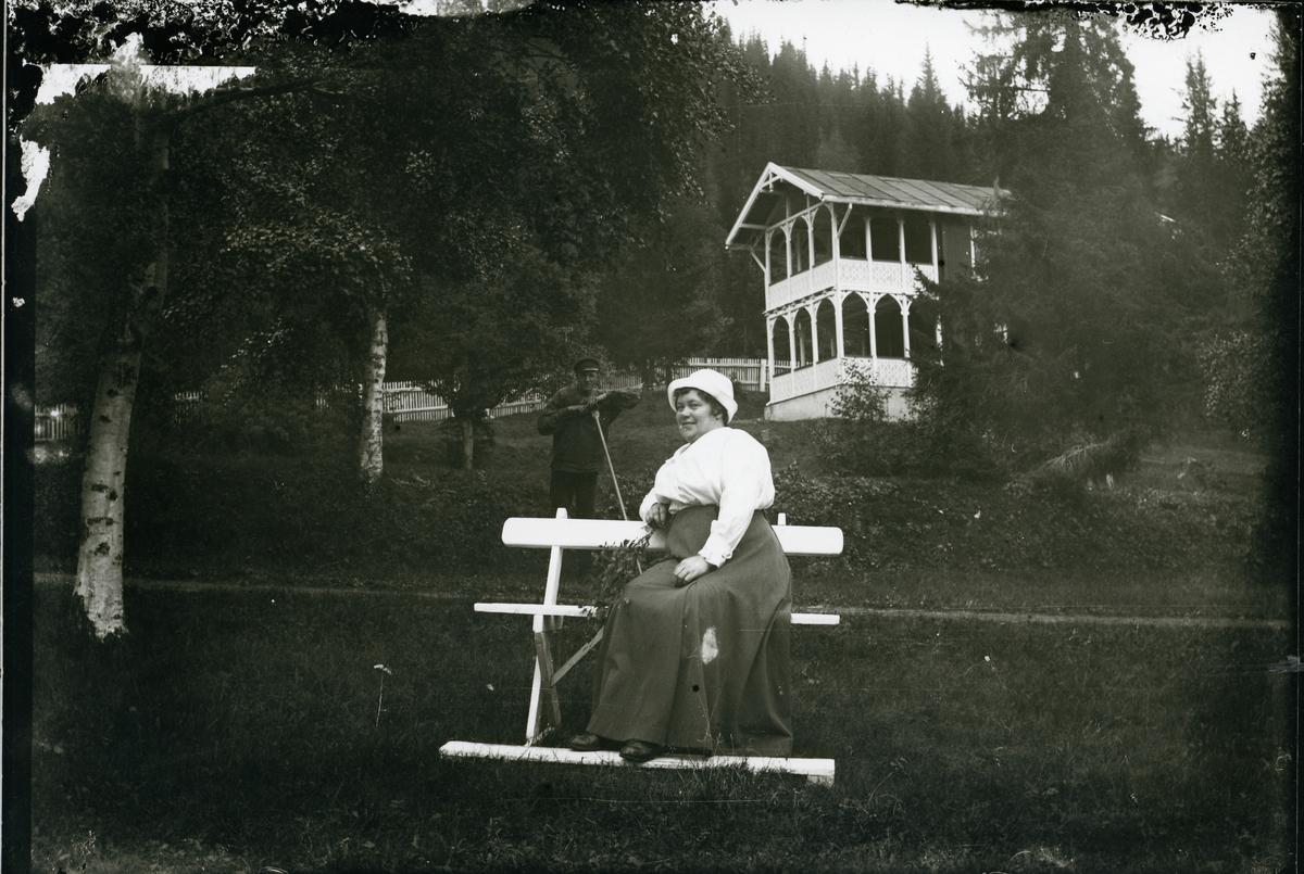 Ei kvinne sit på ein benk ute i ein hage. Bak henne står ein mann med ei rive, ca 1910-1915.