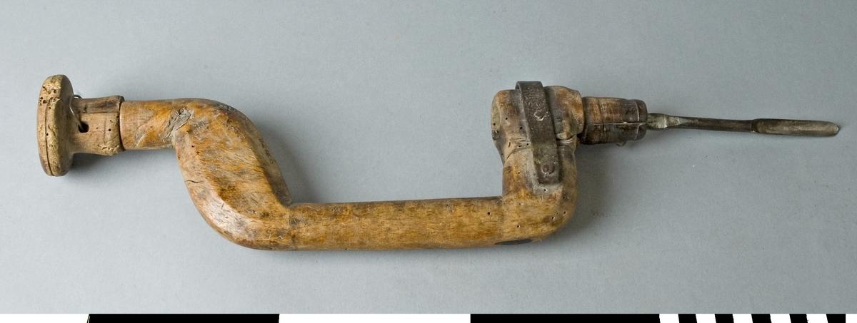 Borrsväng tillverkad i ett helt stycke av björk. Den nedre delen där borrfästet är monterat har gått av och är fastsatt med ett järnband. Den svarvade knoppen är lagad med en ståltråd. Borrsvängen är mycket nött och har flera små hål. Knoppen är sprucken. I borrfästet sitter en skedborr med diameter 10 mm.  Funktion: Handdriven hållare för borrstål