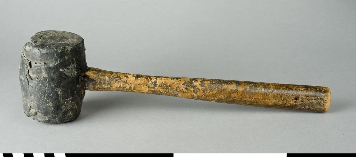 Klubba med skaft av trä och huvud av massivt gummi. I kanterna på slagytan har gummibitar lossnat.  Funktion: Skonsam sammanfogning av trädelar i arbetsstycke