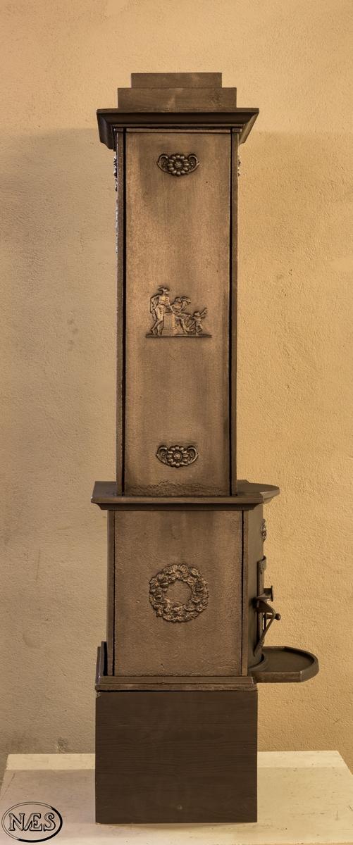 Ovnen har store reine flater og fast komposisjon med tydelig ornamentik. Frontplaten 1.etg har en buet form.Ovnens 2.etg er konstruert for luftoppvarming. Over ileggsdøren en rosett flankert av akantusblad og gjentas under toppgesimsen. En enkel rosett, med nedhengende rosenkvist under, pryder de høye stolpene på siden av det åpne midtpartiet med to hyller. På kortsiden av fyrkassen er det en bladkrans i kraftig relieff, og på den høye stolpen i etasjen ovenfor ser man en figurscene i lavt relieff. Her står handelens gud Merkur ved et alter, og tett ved sitter en kvinne med et overflødighetshorn. Ved alteret ligger et skipsanker, og her flagrer en vinget amorin.Motiv på sideplaten 2.etg: Merkur og Annona med symbolsk barn (antatt usikker).