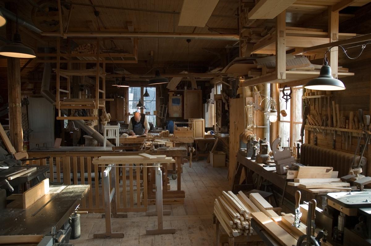 Interiör från Skansens snickerifabrik. Möbelsnickaren arbetar vid sin snickarbänk.