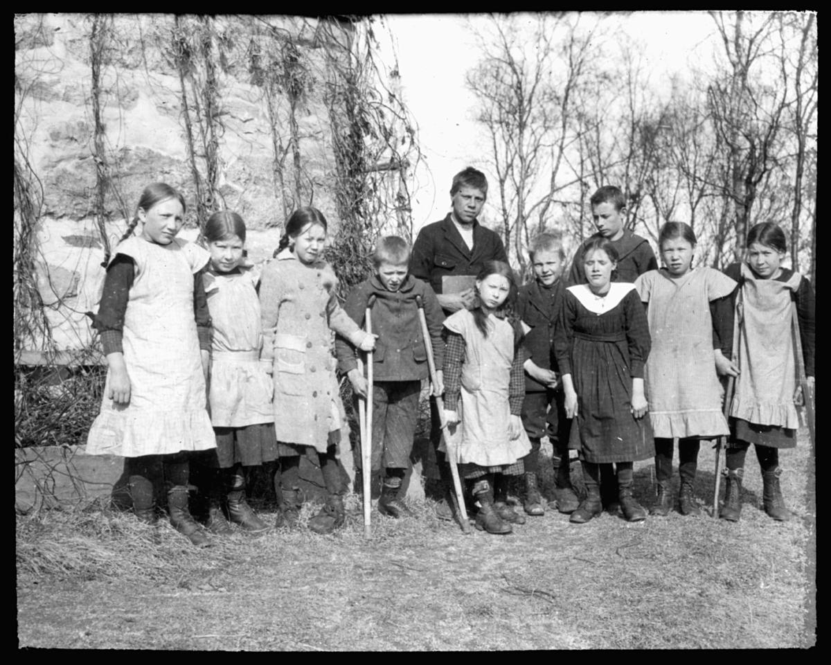 """«N.14b) Fra Vanførehjemmet. G.47» Står det på glassplaten.  Dette er sannsynligvis fra Bjerkely vanførehjem, opprettet av Finnemisjonen i 1913. Bildet er tatt i  1936 og er derfor tatt etter utvidelsen og påbyggingen av Bjerkely. (I boka Finnemisjoen er det beskrevet slik: """"Det var det første skolehjem for vanføre i Norge og det første som fikk statsbidrag. Stedet ble betydelig utvidet og påbygget i 1934, for å gi plass til flere barn. Bjerkly ble drevet som et skoleinternat hvor barna skulle få boklig og praktisk opplæring.""""). Mange som kom hit hadde hatt tuberkulose og polio som følge av sykdommen. Ungene som står med krykker er sannsynligvis angrepet med polio."""
