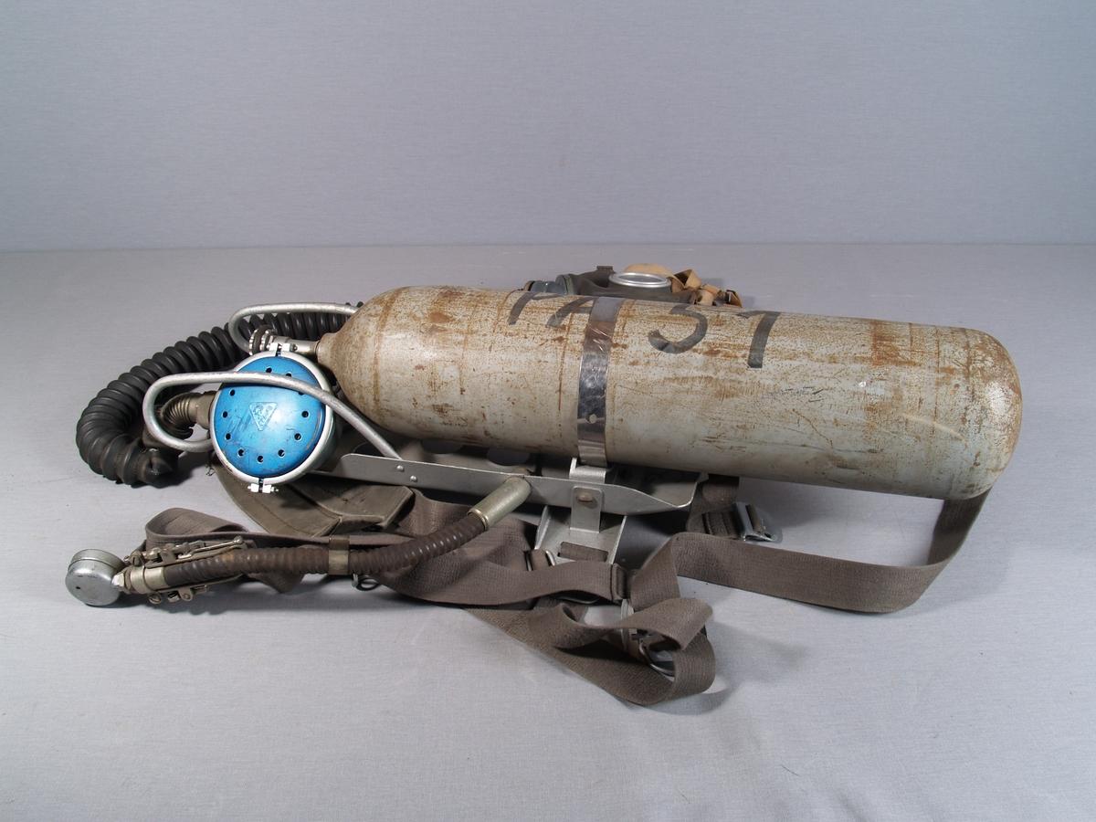 Gassmaske med slange tilkoblet pressluftapparat. Apparatet har bæresele for å bære på ryggen. Trykkmåler på den ene bæreselen.