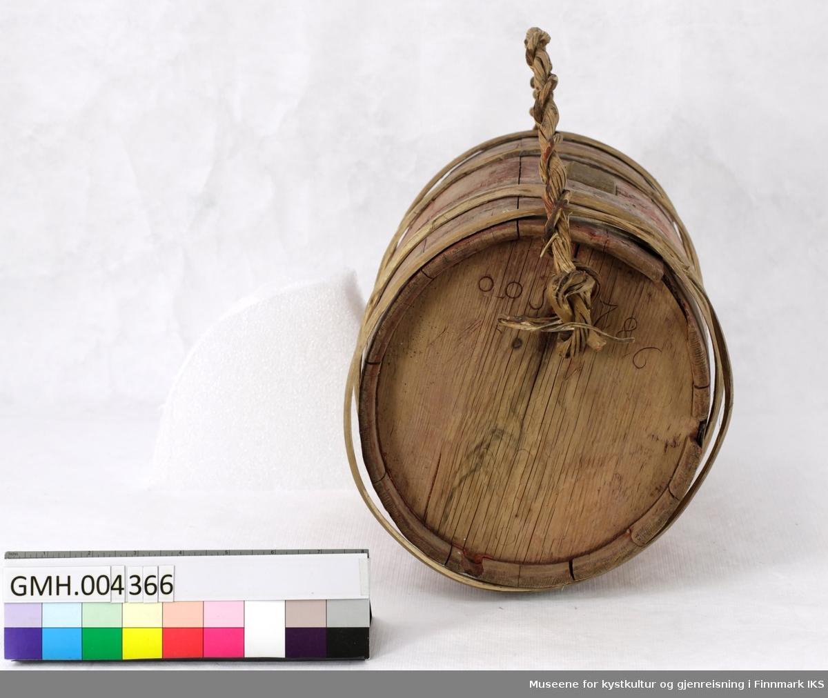 """Oval, rødmalt vinfat med bærehank av vridd tremateriale og en firkantet åpning på øvreside. Fatet er laget av ni tønnestaver og 4 band. På den ene ovalsiden er det innpreget """"ooS 1786"""" mens det den andre siden er pyntet med et mønster av innpregete ringer."""